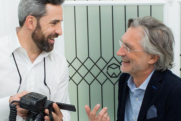 Zahnarzt Dr. Andreas Quidenus in Wien zeigt älterem Patienten die Ergebnisse einer erfolgreichen Behandlung mit Zahnimplantaten auf einer Fotokamera