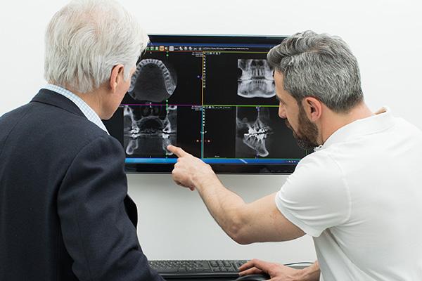 Zahnarzt Dr. Andreas Quidenus zeigt älterem Patienten dreidimensionale Röntgenbilder seines Kiefers