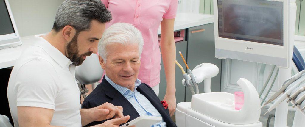 Zahnarzt Dr. Andreas Quidenus in Wien zeigt älterem Patienten das Vorgehen bei einer Wurzelbehandlung