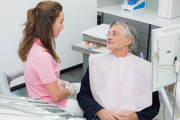 Assistentin der Zahnarztpraxis berät älteren Patienten zur Prophylaxe bei Zahnimplantaten