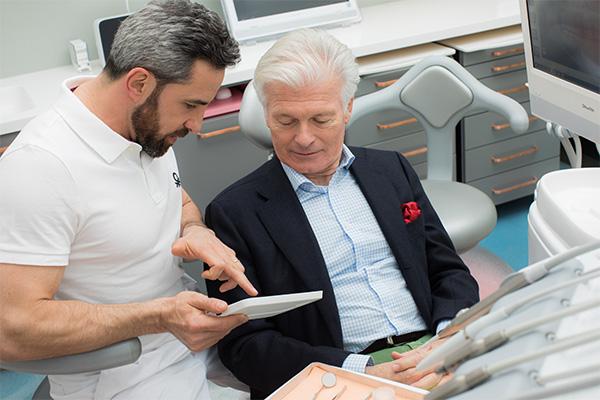 Zahnarzt Dr. Andreas Quidenus erklärt älterem Patienten am Tablet die Möglichkeiten von Zahnimplantaten