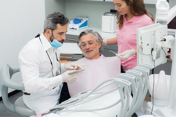 Zahnarzt Dr. Andreas Quidenus wählt zusammen mit älterem Patienten die individuelle Zahnfarbe für den Zahnersatz