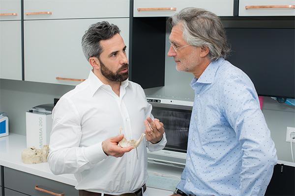 Zahnarzt Dr. Andreas Quidenus in Wien erklärt älterem Patienten die Materialien und Vorgehensweise bei Knochentransplantationen