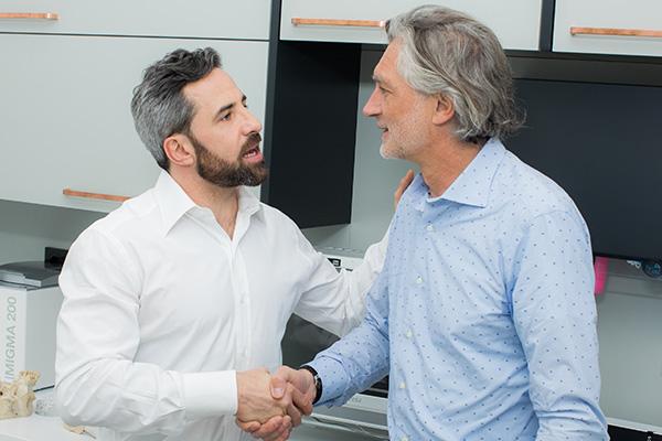 Zahnarzt Dr. Andreas Quidenus begrüßt älteren Patienten zur Behandlung in Wien