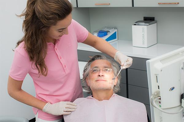 Prophylaxe Expertin beginnt die Prophylaxe Untersuchung bei älterem Patienten im Behandlungszimmer
