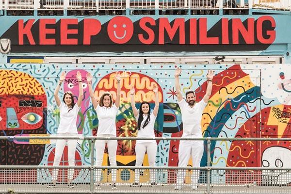 Das Team der Zahnarztpraxis und Zahnarzt Dr. Andreas Quidenus heben entspannt die Hände vor künstlerischer Wand in Wien